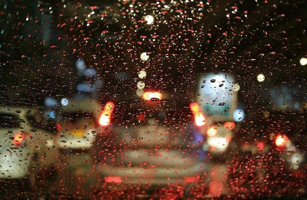 Niewyraźne światła uliczne i lampy ogonowe widoczne przez krople deszczu na szybie samochodu w nocy