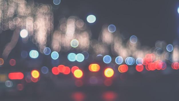 Niewyraźne światła uliczne w nocy. bokeh światła uliczne z samochodów w mieście.