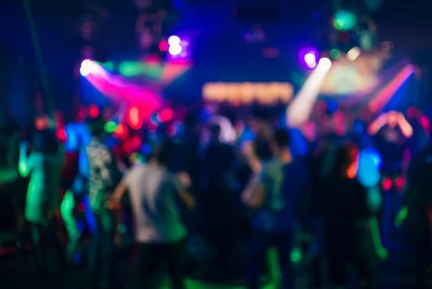 Niewyraźne sylwetki ludzi tańczących w nocnym klubie