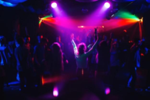 Niewyraźne sylwetki tańczących ludzi na koncercie