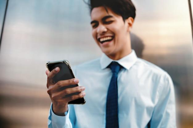Niewyraźne szczęśliwy młody biznesmen za pomocą telefonu komórkowego w mieście. styl życia współczesnych ludzi. przedni widok. stojąc pod ścianą.