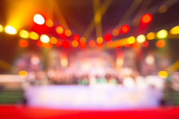 Niewyraźne tło imprezy koncertowej lub ceremonii wręczenia nagród z oświetleniem w sali konferencyjnej