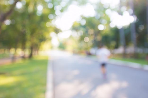 Niewyraźne tło ludzi ćwiczących w parkach na świeżym powietrzu: rozmycie ludzi biegających