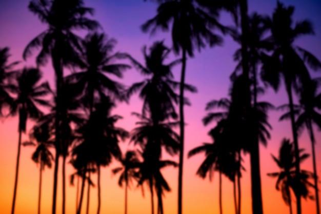 Niewyraźne tło natura sylwetki palm lub drzew kokosowych w tropikalnej plaży o zmierzchu z kolorowym niebem zmierzchu, tajlandia. letnie wakacje lub wakacje ekspres w koncepcji ciepłego kraju.