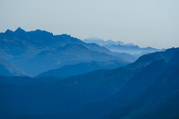 Niewyraźne tło naturalne z kaukazu w porannej błękitnej mgle