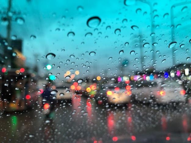 Niewyraźne tło raindrops na przedniej szybie, światło uliczne w nocy w deszczowy dzień.