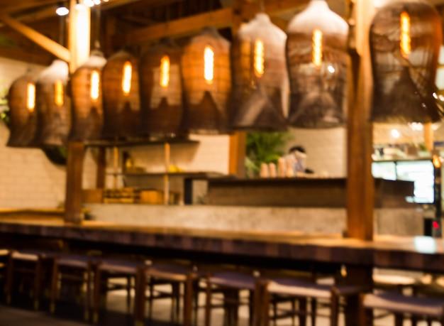 Niewyraźne tło: restauracja ze stołami i krzesłami rozmywa tło światłem bokeh. porą wieczorową
