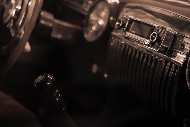 Niewyraźne tło stylizowane na stare monochromatyczne zdjęcie - fragment wnętrza zabytkowego samochodu, skupienie na klamce radia