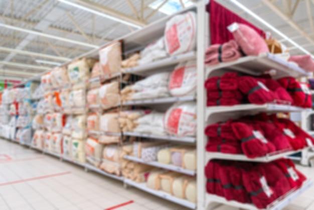 Niewyraźne tło supermarketu. sprzedaż poduszek i pościeli w supermarkecie.
