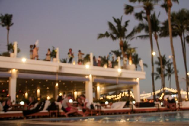 Niewyraźne tło wielu osób bawiło się na imprezie na plaży. świąteczna koncepcja.