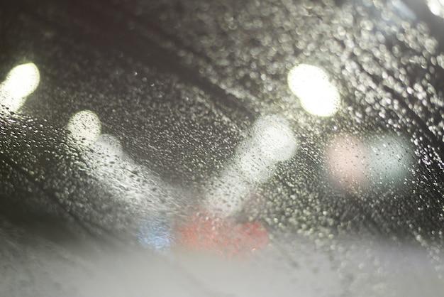 Niewyraźne tło z kroplami deszczu i światłami.