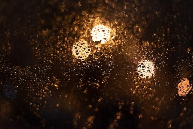 Niewyraźne tło z kroplami deszczu i światłami