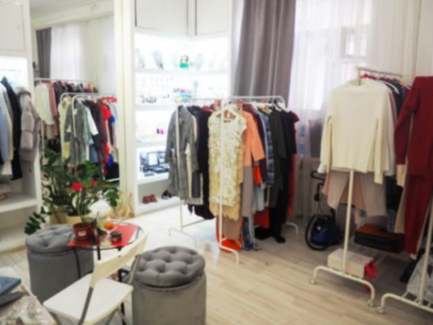 Niewyraźne ubrania na wieszaku w sklepie odzieżowym. abstrakcjonistyczna plama i defocused zakupy centrum handlowe wydziałowego sklepu wnętrze