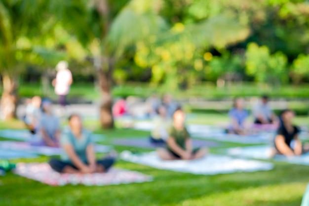 Niewyraźne widok grupy tajskich ludzi było ćwiczeniem jogi w publicznych parkach