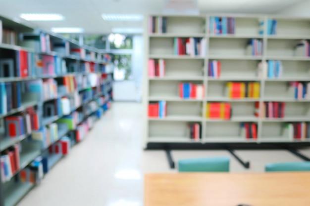 Niewyraźne wnętrze biblioteki publicznej z drewnianymi stołami, krzesłami i książkami na półkach.