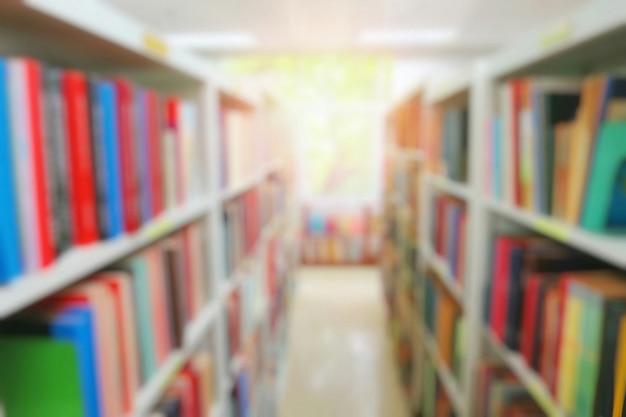 Niewyraźne wnętrze biblioteki publicznej z książkami w drewnianych regałach. dzień edukacji i książki.