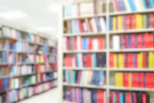 Niewyraźne wnętrze biblioteki z książkami na półkach. koncepcja dnia edukacji i książki.