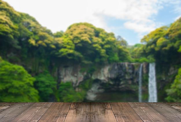 Niewyraźne wodospad cheonjiyeon jest wodospadem na wyspie jeju, korea południowa z drewnianym mostem.