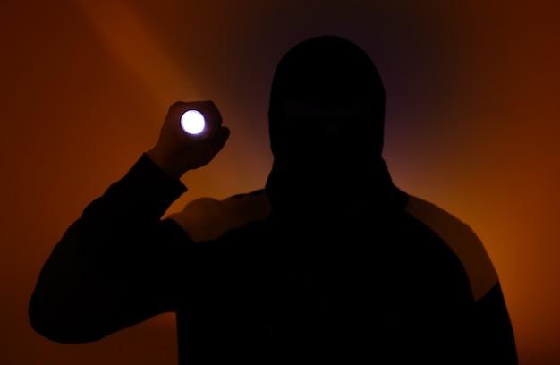 Niewyraźne zdjęcie. włamywacz w ciemnych ubraniach trzymający latarkę. niebezpieczny złodziej w masce z pochodnią. przestępca.