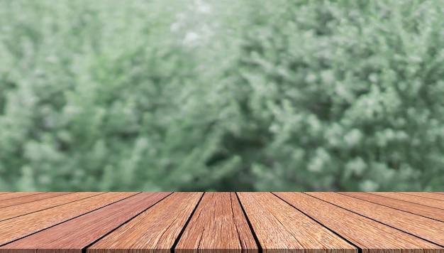 Niewyraźne zielone liście z tłem stołu z drewna