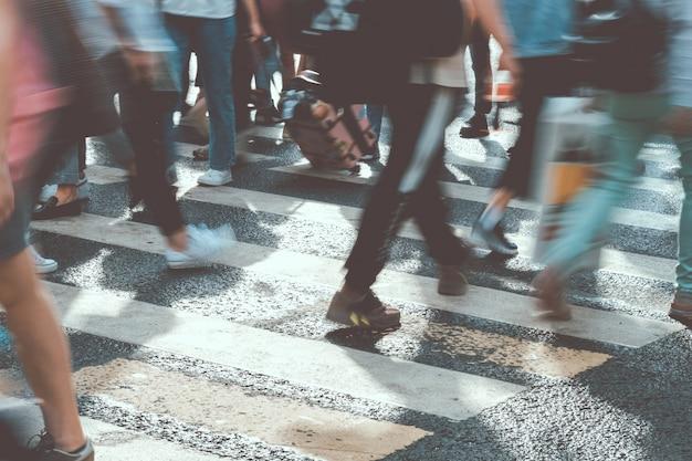 Niewyraźni ludzie spacerują po słonecznym mieście stonowanych