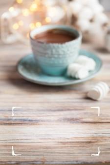 Niewyraźny drewniany stół i kubek gorącego kakao