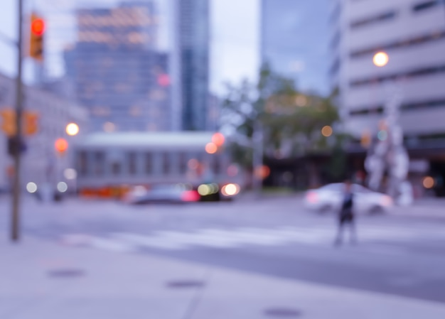 Niewyraźny mężczyzna chodzący na przejściu dla pieszych przez ulicę w mieście z jasnym tłem bokeh