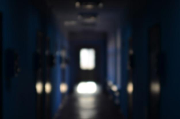 Niewyraźny obraz ponurego korytarza zaniedbanego budynku publicznego.