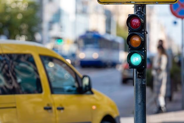 Niewyraźny obraz ruchu miejskiego z sygnalizacją świetlną, na pierwszym planie sygnalizacja świetlna z zielonym światłem