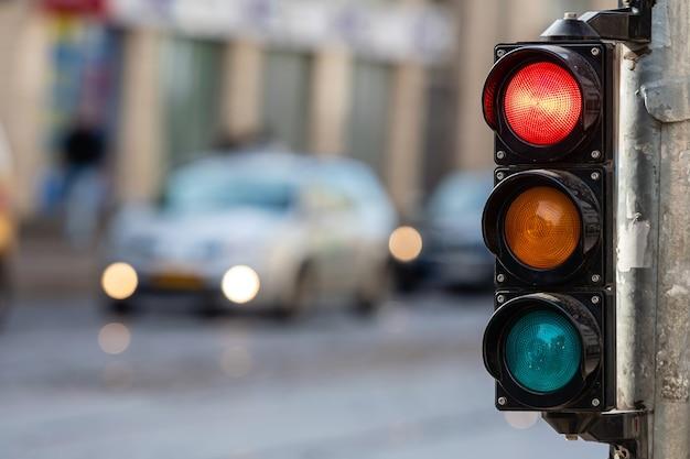Niewyraźny obraz ruchu miejskiego ze światłami, na pierwszym planie semafor z czerwonym światłem