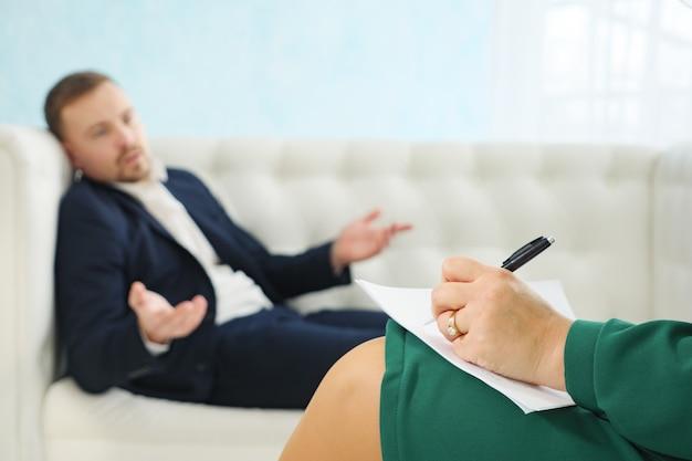 Niewyraźny widok młodego biznesmena siedzącego na kanapie, rozmawiającego ze swoim terapeutą podczas sesji terapeutycznej, selektywne skupienie się na psychologu