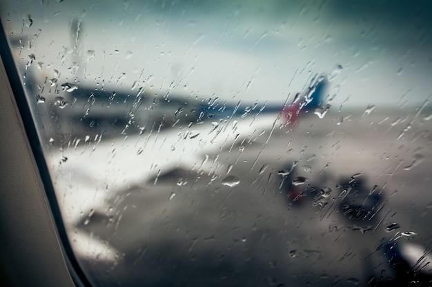 Niewyraźny widok na skrzydło samolotu przez okno pasażera z kroplami deszczu
