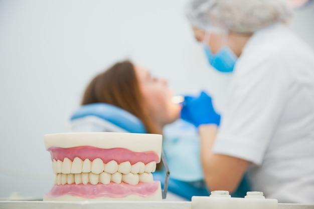 Niewyraźny, zamazany obraz dentysty z pacjentem w biurze kliniki. stomatolog wykonujący leczenie zębów w szpitalu.