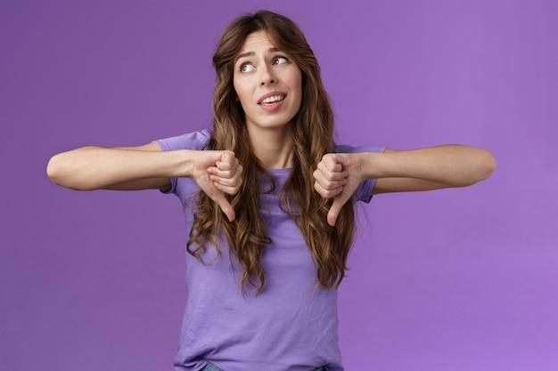 Niewzruszona ignorancja snobistyczna atrakcyjna kędzierzawa dziewczyna nie zgadza się kiepski pomysł odwraca wzrok rozczarowany pokaż kciuk w dół niechęć gest dezaprobaty nie jest zainteresowany zdenerwowanym fioletowym tle.