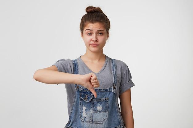Niewzruszona niechęć do atrakcyjnej kobiety w kombinezonie dżinsowym, pokazująca kciuk w dół i uśmiechająca się z niezadowolenia