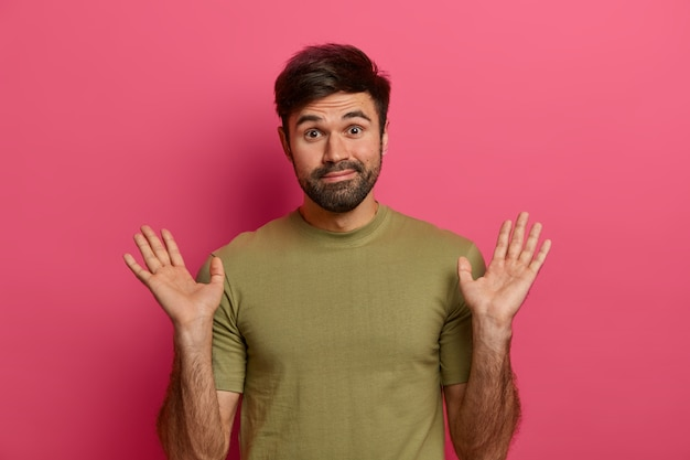 Niezaangażowany mężczyzna unosi dłonie i nosi zwykłe ubranie