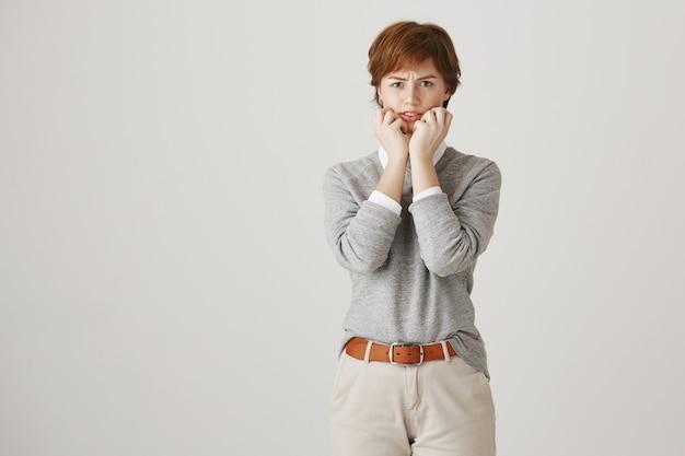 Niezabezpieczona ruda dziewczyna z krótką fryzurą pozuje przy białej ścianie