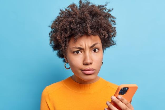 Niezadowolenie afro american kobieta uśmiecha się twarz wygląda z niezadowolonym wyrazem posiada nowoczesne komórkowe odczytuje negatywne wiadomości online nosi pomarańczowy sweter izolowany nad niebieską ścianą. koncept technologiczny