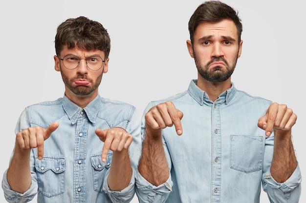 Niezadowolenie dwóch braci ma ponure miny, trzyma palce wskazujące w dole, nosi dżinsowe koszule, czuje się niezadowolony