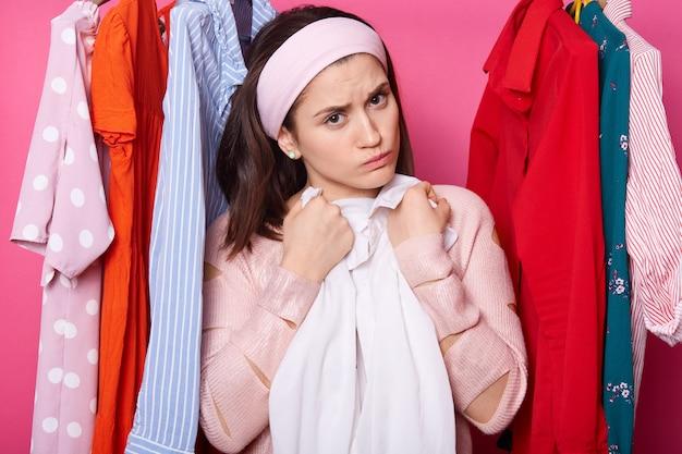 Niezadowolenie młodej kobiety obejmuje białą bluzkę. piękna kobieta nosi różany sweter i opaskę do włosów. zdenerwowana dziewczyna z dużą ilością ubrań w szafie. urocza dama odizolowywająca nad menchii ścianą mody pojęcie.