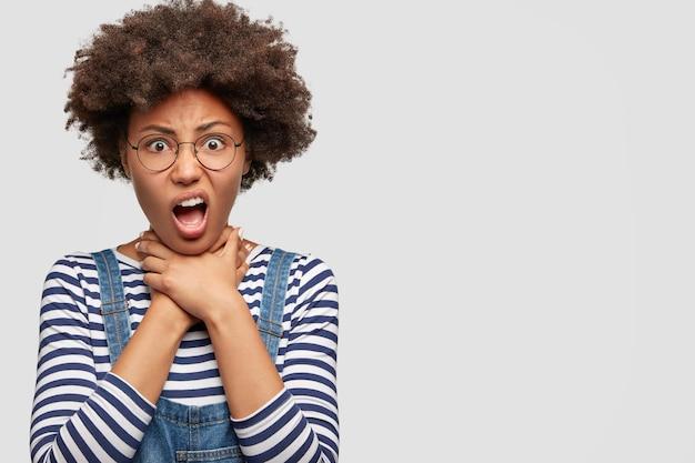 Niezadowolenie zirytowana młoda kobieta udusi się, szeroko otwiera usta, ma dość codziennej rutyny