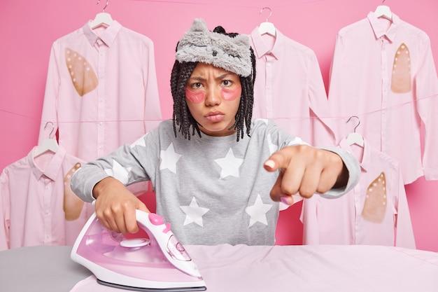 Niezadowolona afro amerykanka wskazuje bezpośrednio na aparat, ma wyraz niezadowolenia, nosi piżamę w pociągnięciach, ubrania w pobliżu deski do prasowania, poddawana jest zabiegom kosmetycznym izolowanym na różowej ścianie