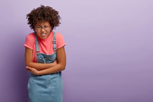 Niezadowolona afroamerykanka trzyma ręce na brzuchu, zaciska zęby z powodu nieprzyjemnych uczuć, ma dolegliwości lub bóle menstruacyjne, czuje dyskomfort w brzuchu, nosi dżinsową sarafan.