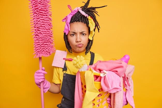 Niezadowolona afroamerykanka w gumowych rękawiczkach na głowie trzyma mopa