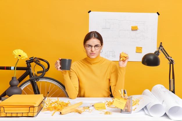 Niezadowolona architektka marszczy brwi, jest niezadowolona ze swojego projektu architektonicznego, zgniata papiery, pije kawę, nosi okulary, golf siedzi przy biurku