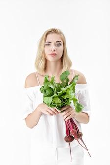 Niezadowolona blond kobieta w białej bluzce trzyma buraka z zielonymi liśćmi na białym tle. zdrowie i witaminy