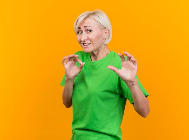 Niezadowolona blond słowiańska kobieta w średnim wieku, patrząc na przód, nie robiąc żadnego gestu na żółtej ścianie z miejscem na kopię