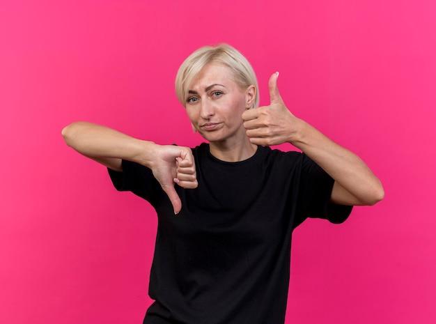 Niezadowolona blond słowiańska kobieta w średnim wieku, patrząc z przodu pokazując kciuki w górę iw dół odizolowane na różowej ścianie