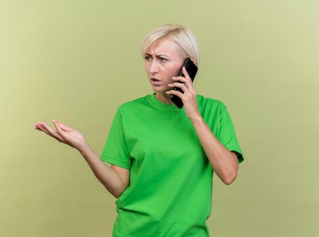 Niezadowolona blond słowiańska kobieta w średnim wieku rozmawia przez telefon patrząc w bok, pokazując pustą dłoń odizolowaną na oliwkowej ścianie z miejscem na kopię