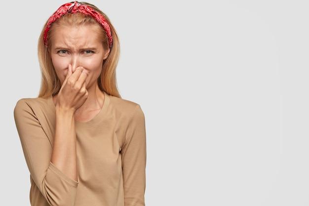 Niezadowolona blondynka młoda kobieta pozuje na białej ścianie